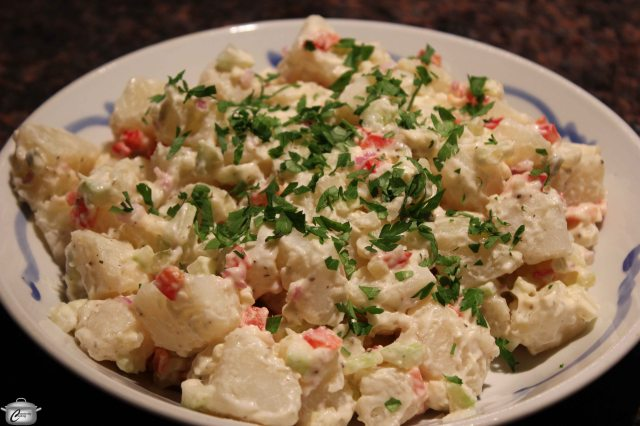 Putting the vinegar directly on the hot potatoes rather than in the mayonnaise mixture makes for subtly tangy potato salad that outshines all others I've tasted.