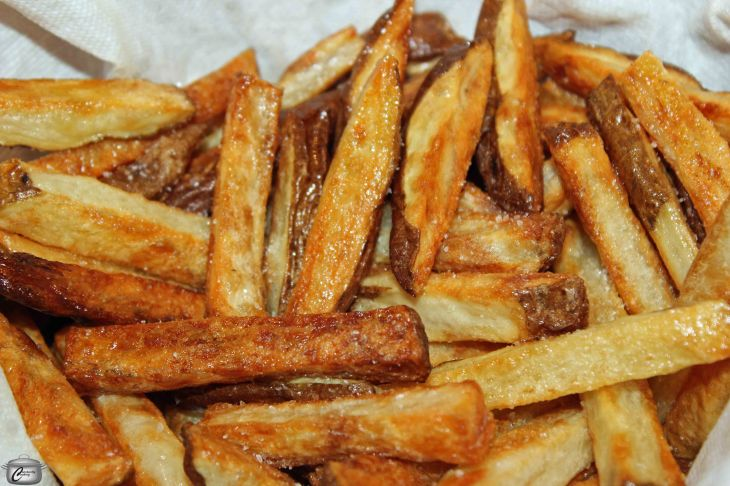 For the best oven-baked fries, parboiling them in a water and vinegar solution prior to baking them is the secret to making them as crispy as though they'd been deep fried.