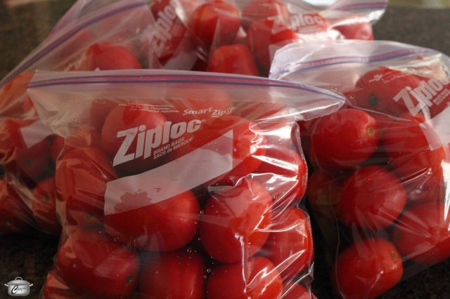Freezing whole, unpeeled tomatoes is the fastest method and allows you to then cook with them in smaller batches throughout the winter.
