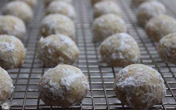 Toss the still-warm cookies in powdered sugar and then apply a second coating once they have cooled completely.