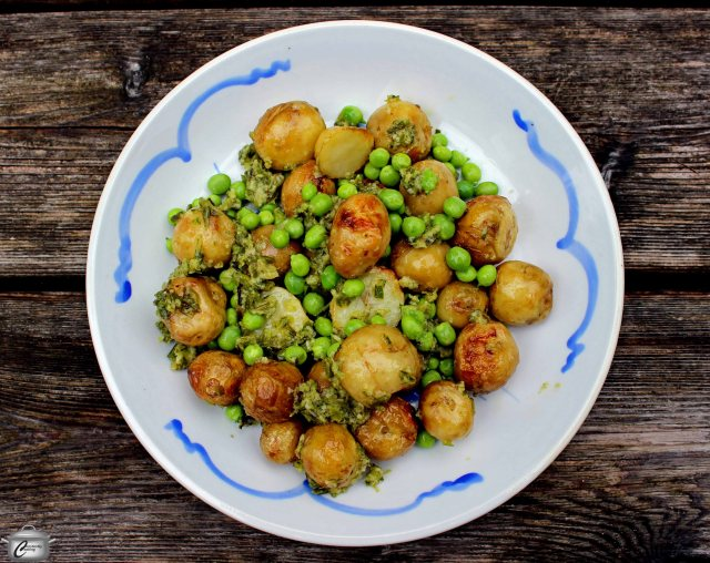 New potatoes and peas are dressed up with a pesto made with grilled garlic scapes.