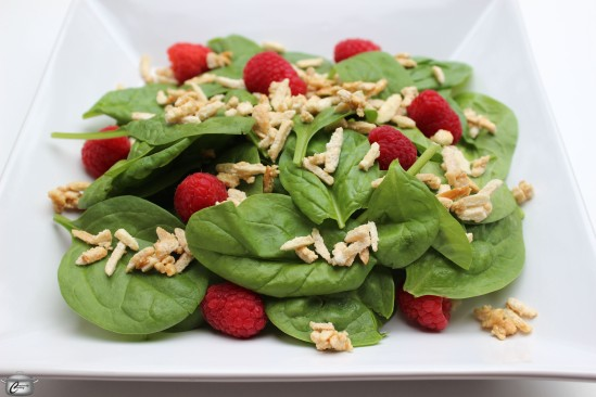 The bright, fresh tastes of spinach and raspberries are perfectly complemented by crunchy candied almonds and a tangy vinaigrette.