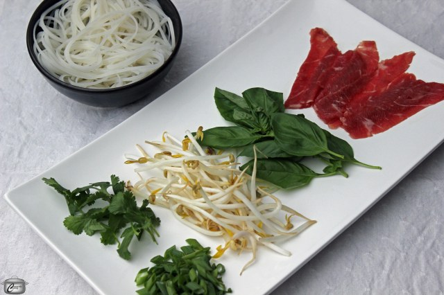 Basil, cilantro, green onions and beansprouts are common Pho toppings to accompany rice noodles and thinly sliced steak.