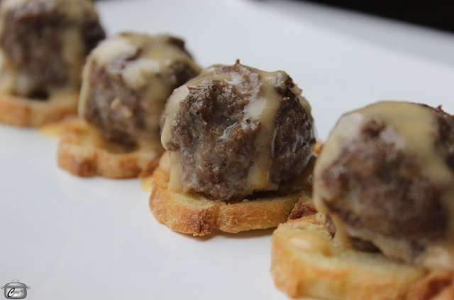 Meatballs stuffed with smoked Cheddar and drizzled with a Cheddar-Beer sauce will steal the show at your next party.